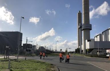 collega's port of Amsterdam die op een haventerrein zwerfvuil opruimen