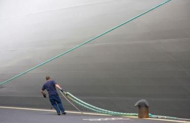 havenwerker legt schip aan kade en bolder aan