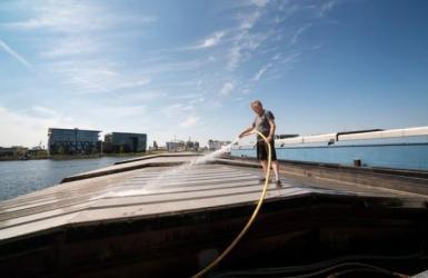 Binnenvaartschipper spuit dek schip schoon